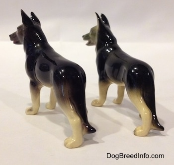 The back left side of two black with white German Shepherd standing figurines. The figurines tails are going down there legs.