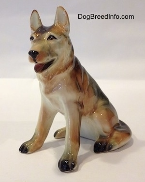The front left side of a ceramic figurine of a black with tan and white German Shepherd sitting. The figurines ears are standing.