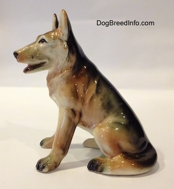 The left side of a ceramic black with tan and white figurine of a sitting German Shepherd. The figurine has detailed black circles for eyes.