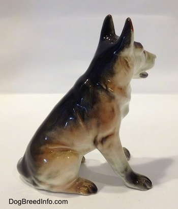 The right side of a figurine of a ceramic sitting German Shepherd. The figurine has long legs.