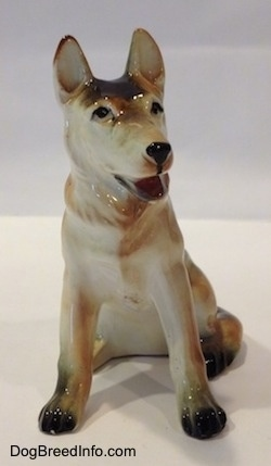 A black with tan and white ceramic German Shepherd sitting figurine. The figurine has its mouth painted open and black circles for eyes.