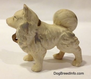 The left side of a ceramic white with gray German Spitz figurine. The figurine has a tail laid on its back.