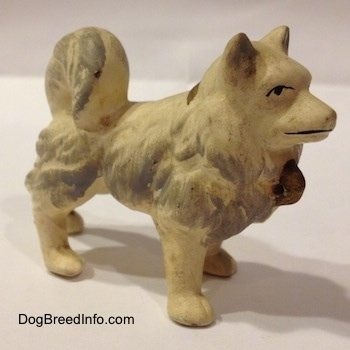 The right side of a German Spitz ceramic dog figurine. The figurine is white with gray brushings.