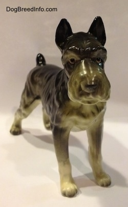 A black, grey and white figurine of a bone china Giant Schnauzer. The figurine has black circles for eyes.