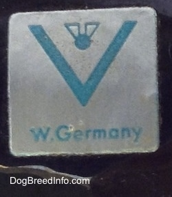 Close up - On the underside of a figurine there is a sliver and blue sticker that has a full bee inside the V logo and under that are the words - W.Germany.