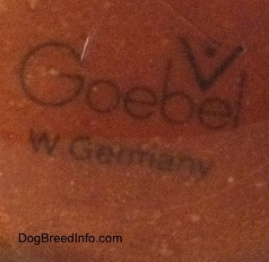 Close up - The underside of a brown figurine that is scratched and the stamp of Goebel W.Germany is on it.