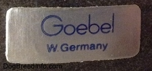 "The silver and blue rectangle sticker with the name ""Goebel"" with W. Germany"" below it."