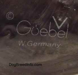 Close up - The underside of a black figurine with the Goebel W.Germany logo chalked into the bottom of the figurine.