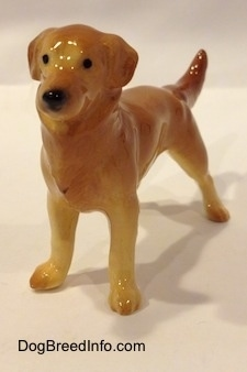 The front left side of a figurine of a brown with tan Golden Retriever. The figurine has black circles for eyes.