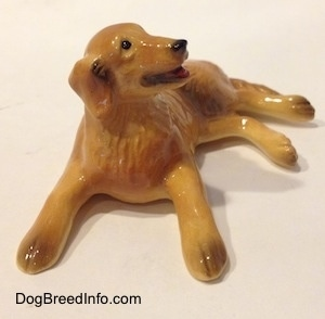 A figurine of a Golden retriever in a laying down pose. The figurine has brown tipped paws.
