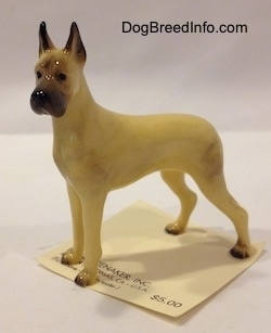 The left side of a figurine of a tan with black Great Dane. The figurine has large black tipped ears.