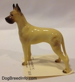 The left side of a figurine of a tan with black Great Dane. The figurine has a long body and it is glossy.