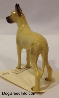 The back left side of a tan with black Great Dane figurine that has a long tail.