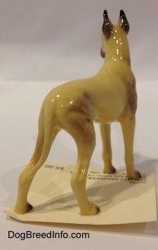 The back right side of a figurine of a tan with black Great Dane figurine. The figurine has long tan legs and small black paws.