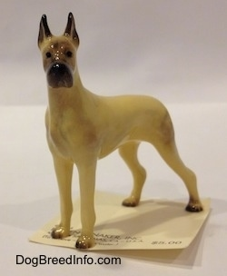 The front right side of a tan with black Great Dane figurine. The figurine has black circles for eyes.