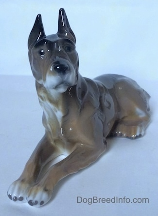 The front left side of a Great Dane figurine in a laying down pose. The figurine has black circles for eyes and its ears are sticking up.