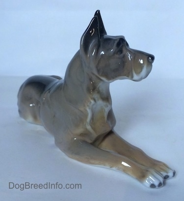 The front right side of a figurine of a Great Dane in a laying down pose. The figurine has fine chest hair details.