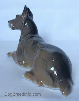 The back left side of a Great Dane laying down figurine. The figurine has a long body.
