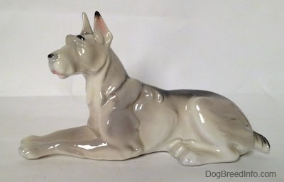 The left side of a white with black Great Dane laying down figurine. The figurine has a long body and a black spot on its back.