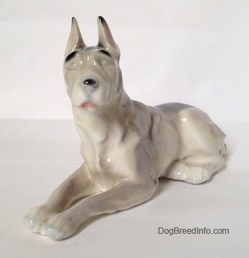 The front left side of a figurine of a white with black Great Dane laying down figurine. The figurine has long legs and small paws.