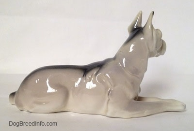 The right side of a white with black Great Dane laying down figurine. There is a black strip going across the body of the figurine.