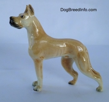 The left side of a tan Great Dane figurine. The figurine has long legs that lead to small paws with black nails.