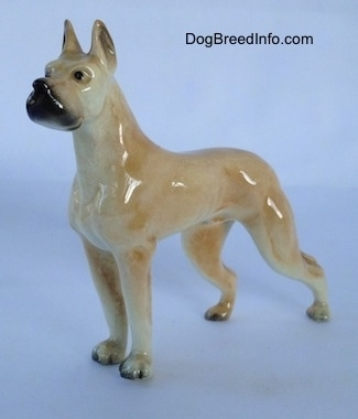 The front left side of a figurine of a tan Great Dane. The figurine has a black muzzle.