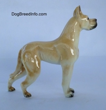 The right side of a figurine of a tan Great Dane. The figurine is glossy.