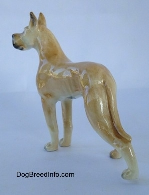 The back left side of a tan figurine of a Great Dane. The figurine has a long detailed body.