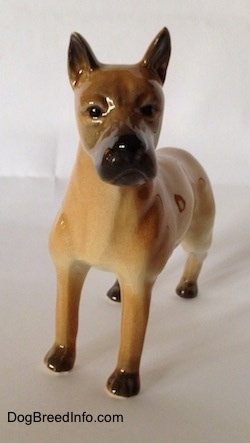 A tan Great Dane figurine in a standing pose. It has a detailed face and black circles for eyes.