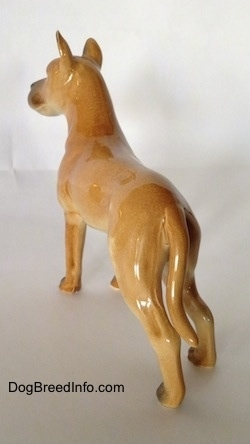 The back left side of a tan Great Dane figurine. The figurine has a long tail and its ears are sticking up.
