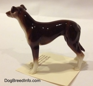 The left side of a brown with white Greyhound figurine. The figurine has a long slender body.