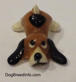 A brown with white and black Hound Dawg figurine is laying down and it has a black spot near its tail.