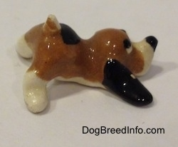 The right side of a Hound Dawg figurine that has long black ears laying on the ground.