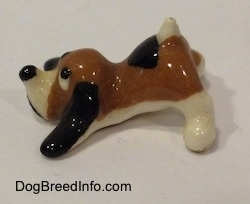The left side of a figurine of a brown with white and black Hound Dawg figurine. The figurine has its front on the ground and its back side in the air.