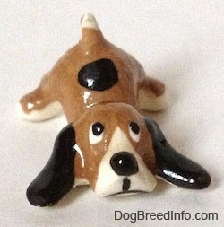 A brown with white and black spotted Hound dog figurine is laying down. The figurine has long black ears laying out.