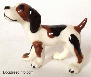 The left side of a white with brown and black vintage Hound dog in a standing pose figurine. The dog has long drop ears, a short docked tail that is up in the air, a black nose and black eyes.