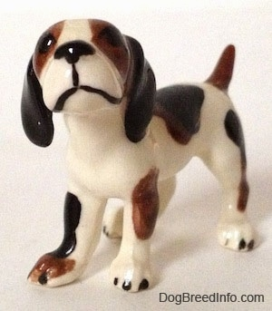 The front left side of a white with brown and black vintage Hound dog figurine. The figurine has long black ears. The nose and mouth are painted black.