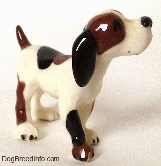 The front right side of a vintage Hound dog figurine. The figurine has a very glossy outside. The dog is looking upward.
