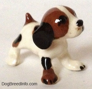 The front right side of a white with brown and black vintage Hound dog figurine with black circles for eyes.