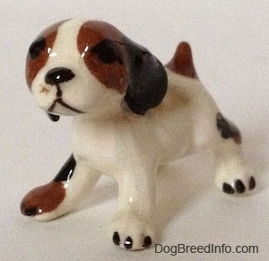 The front left side of a white with brown and black Hound dog figurine that has large black ears attached to the side of its head.