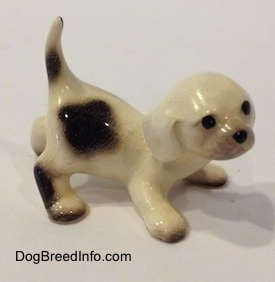 The right side of a white with brown Hound puppy figurine that is crouching. The figurine has black circles for eyes and a nose.