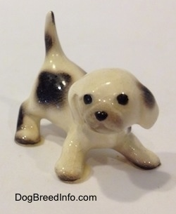 The front right side of a white with brown spotted Hound puppy figurine in a crouching position. The figurine has its tail in the air.