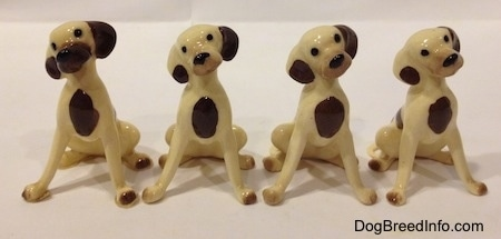 Four miniature Hound Dog Mama figurines have brown spots on there chests and there heads are tilted to the left.