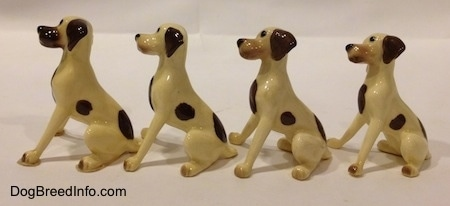 The left side of four white with brown spots Miniature Hound Dog Mama figurine. The figurines have completely brown left ears.