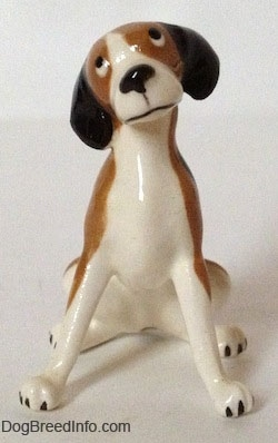 A brown and white with black vintage figurine that is in a sitting pose. The figurines head is tilted to the left and it has long legs with black nails for paws.