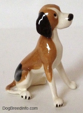 The right side of a white and brown with black spots vintage Hound dog figurine. The figurine has long black ears attached to the side of its head.