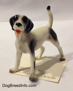 The front left side of a figurine of a white with black dog. The figurine has its mouth open and it looks like it is smiling.