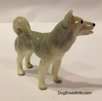 The front right side of a Husky figurine. The tail of the figurine has its tail arched onto its back.