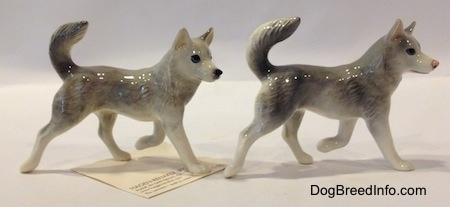 The right side of two grey and white Husky figurines. Both figurines have a paww in the air.